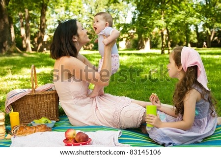 Mother and her two children having picnic in park, playing with baby - stock photo