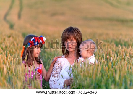 Mother and her two daughters in a field of wheat - stock photo