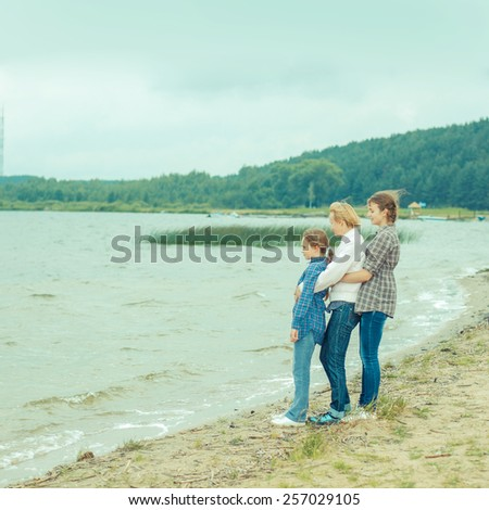 mother and her two daughters on the shore - stock photo