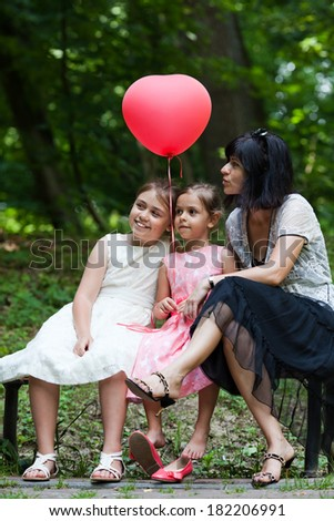 Mother and her two daughters with balloon sitting on bench in the park at summer day - stock photo