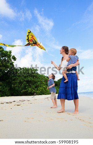 Mother and her two kids flying kite on white sand tropical beach - stock photo