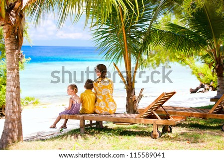Mother and her two kids on vacation enjoying ocean view
