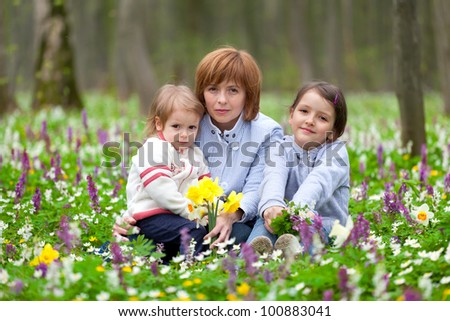 Mother and her two little daughters picking flowers in the spring forest - stock photo