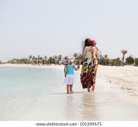 Mother and her two little daughters walking on the beach - stock photo