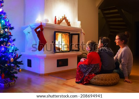 Mother and her two little kids sitting by a fireplace in their cozy family home enjoying Christmas eve - stock photo