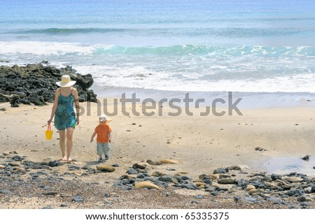Mother and her two year old boy carrying water from the sea in a toy bucket; Graciosa, Canary islands, Spain - stock photo