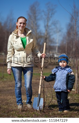Mother and her 2-3 years old boy gardening - stock photo