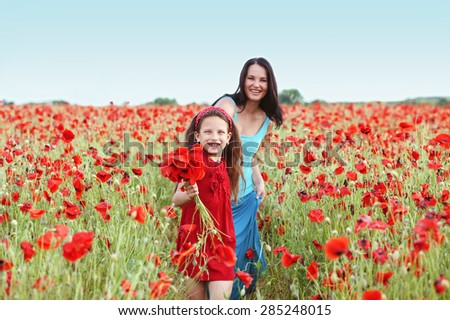 Mother and her 7 years old preteen child playing in spring flower field - stock photo