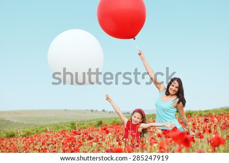 Mother and her 7 years old preteen child playing with big balloons in spring flower field - stock photo