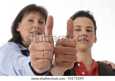 "Mother and her young son stand next to each other, doing the ""thumbs up"" gesture, isolated on white background. - stock photo"