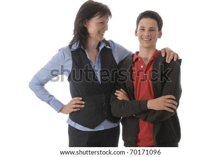 Mother and her young son stand next to each other, is proud and hugged the boy in front of white background. - stock photo