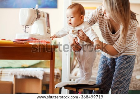 Mother and infant at home, the baby first steps, natural light. Child care and work at home.  - stock photo