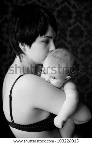 mother and infant calm and gentle hug, infant buried his mother in the shoulder and quietly looking at the light, the picture is black and white