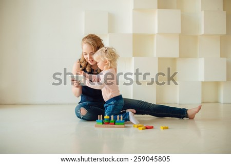 mother and kid are looking to play and read tablet computer - stock photo