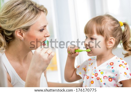 mother and kid brushing teeth in bathroom - stock photo