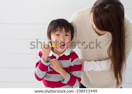 Mother and kid brushing teeth together - stock photo