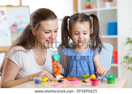 Mother and kid daughter at home molded from clay and play together. Concept of preschool or home education. - stock photo