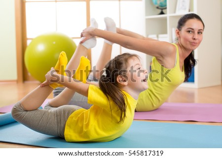 Mother and kid daughter doing yoga exercises on rug at home.