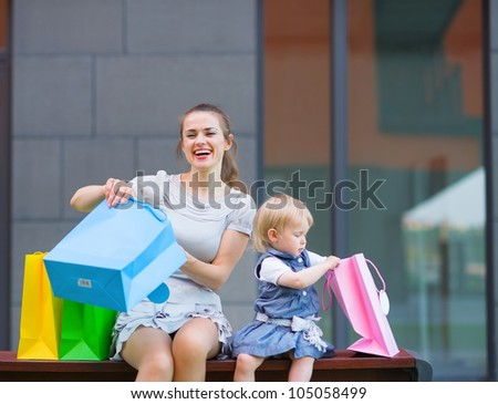 Mother and kid examines purchases after shopping - stock photo