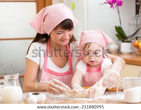 Mother and kid girl bake cookies together at kitchen - stock photo