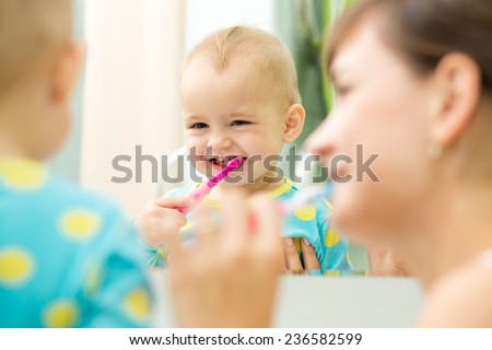 mother and kid girl look at mirror during teeth brushing - stock photo