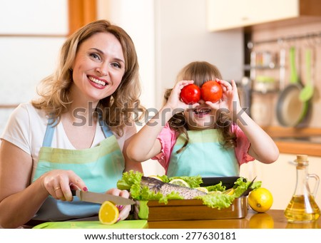 mother and kid have fun cooking in kitchen - stock photo
