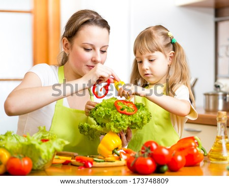 mother and kid having fun at kitchen - stock photo