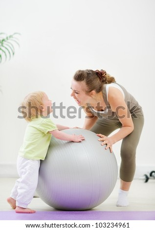 Mother and kid having fun in gym - stock photo
