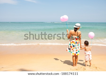 Mother and  kid on the beach with pink balloons, happy mothers day - stock photo