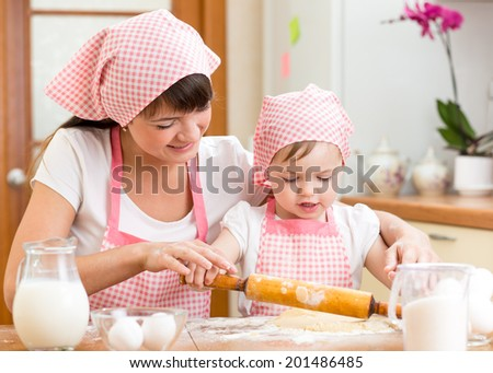 Mother and kid prepare cookies using a rolling pin - stock photo
