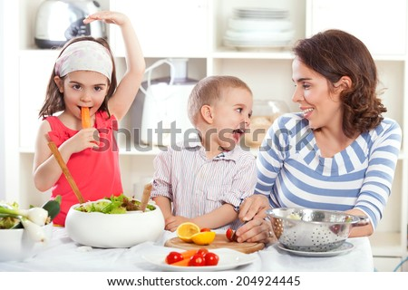 Mother and kids having fun in the kitchen making salad