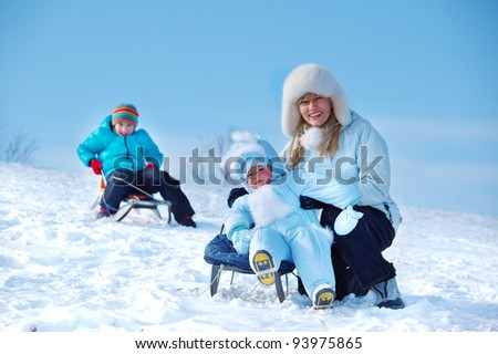 Mother and kids having fun on snowy hill - stock photo