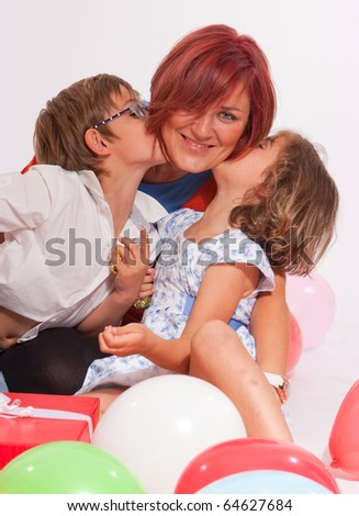 Mother and kids kissing their mum in a Birthday - stock photo