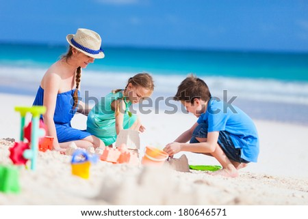 Mother and kids making sand castle at tropical beach