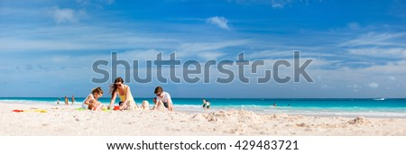 Mother and kids making sand castle at tropical beach - stock photo