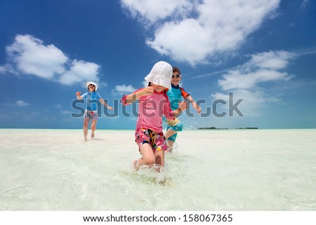 Mother and kids on a Caribbean vacation running at shallow water - stock photo