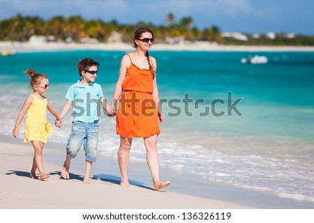 Mother and kids on a Caribbean vacation walking along a beach - stock photo