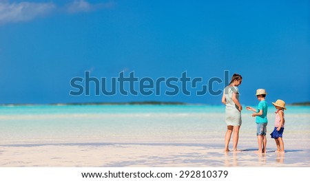 Mother and kids on a remote tropical beach enjoying Caribbean summer vacation - stock photo