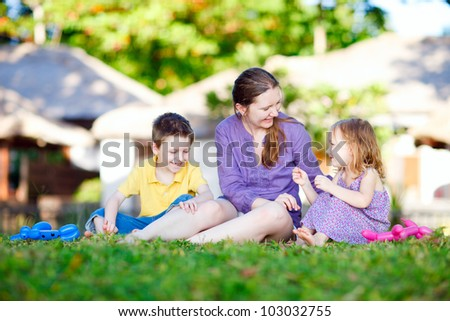 Mother and kids outdoors on beautiful summer day