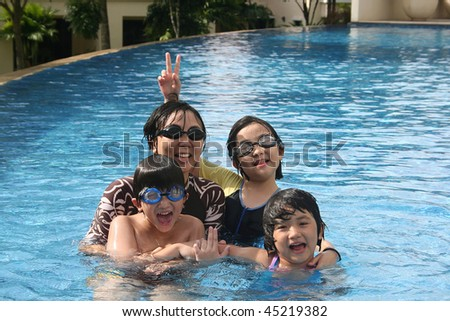 Mother and kids playing happily in the pool