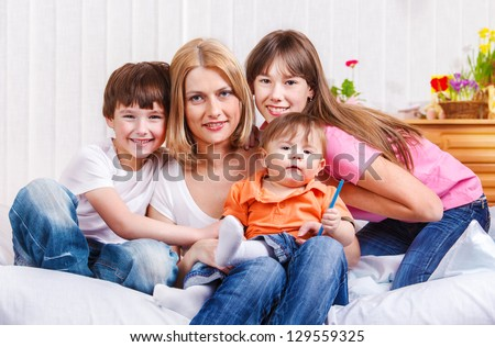 Mother and kids sitting on the bed - stock photo