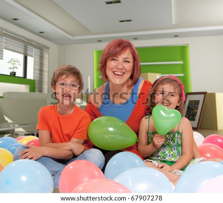 Mother and kids surrounded by balloons in a home interior - stock photo