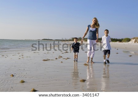 Mother and kids walking on a beach.  Ocean in the background. - stock photo