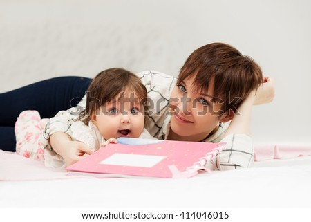 Mother and little baby girl reading a book on bed - stock photo