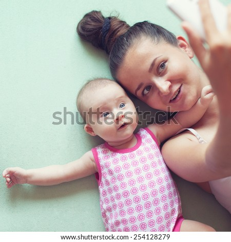mother and little baby taking selfie  - stock photo