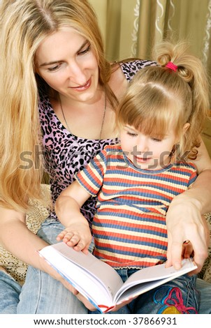 Mother and little blond girl reading