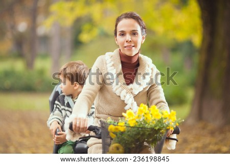 Mother and little boy on a bike enjoying beautiful autumn day - stock photo