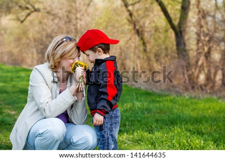 Mother and little boy with dandelion, outdoor
