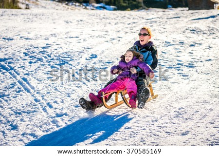 Mother and little child are sledging very fast in ski mountain resort. High speed braking. Active family vacation on snow in the nature. - stock photo