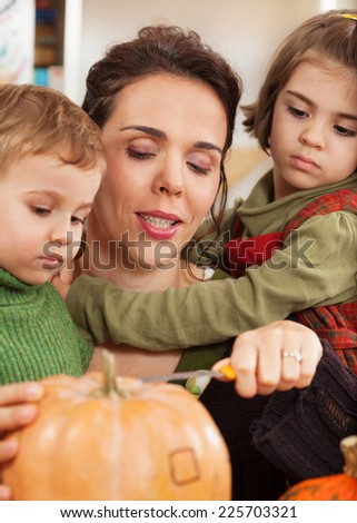 Mother and little children carving pumpkins for Halloween - stock photo